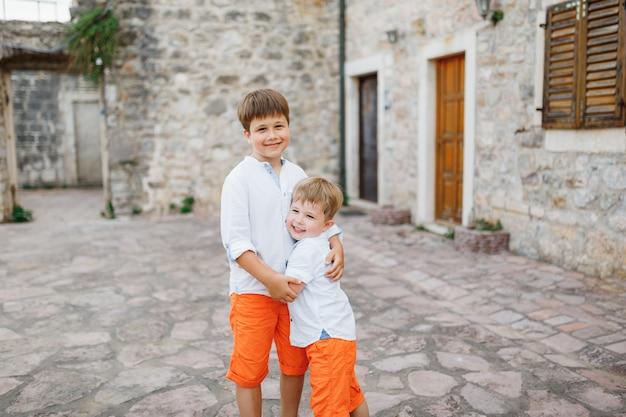 Zwei kleine jungs in orangefarbenen shorts und weißen t-shirts umarmen sich auf der straße in der nähe eines alten