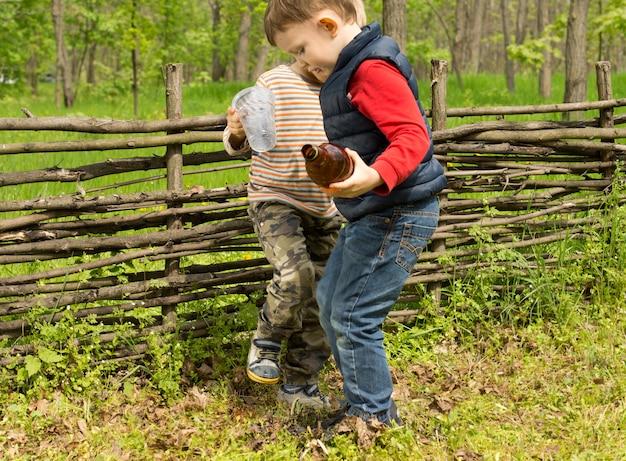 Zwei kleine jungs stampfen ein feuer auf einer wiese aus