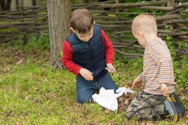 Zwei kleine jungs versuchen ein feuer anzuzünden