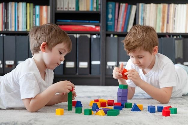 Zwei kleine kaukasische jungen spielen mit holzspielzeug montessori materialien
