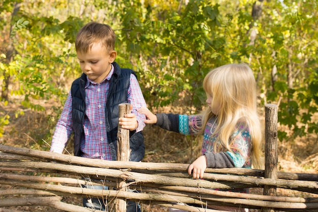 Zwei kleine kinder, die an einem rustikalen holzzaun aus verflochtenen ästen spielen, wobei das kleine mädchen den arm des jungen berührt