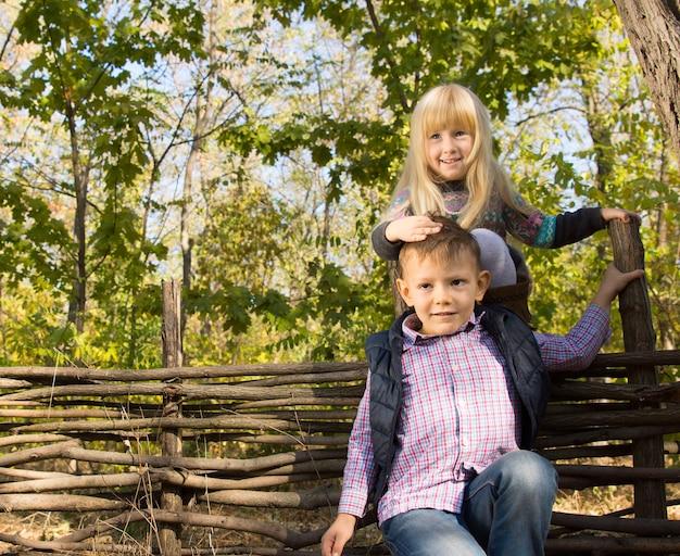 Zwei kleine kinder, die draußen im wald spielen, wobei das kleine mädchen auf einem rustikalen holzzaun balanciert, das sich an der stirn des jungen festhält, um das gleichgewicht zu halten, beide lächeln in die kamera