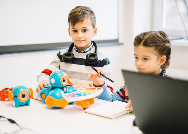 Zwei kleine kinder, die mit digitalen spielwaren im klassenzimmer spielen