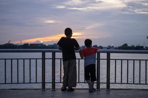 Zwei kleine kinder, die schauend zum meer während des sonnenuntergangs stehen