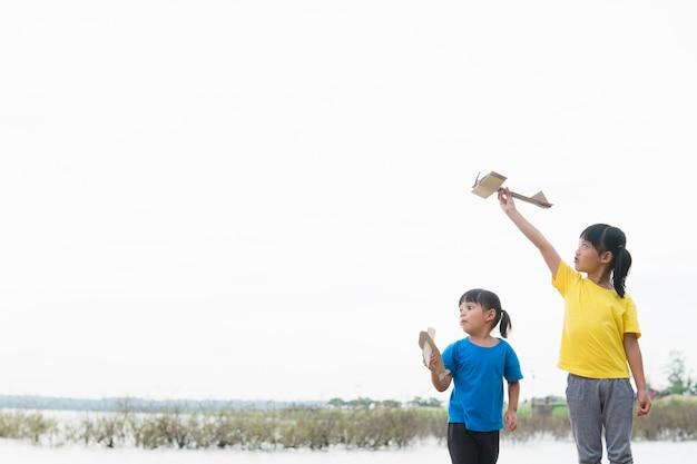 Zwei kleine kinder, die tagsüber mit pappspielzeugflugzeug im park spielen.