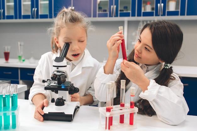 Zwei kleine kinder im laborkittel lernen chemie im schullabor. junge wissenschaftler in schutzbrillen machen experimente im labor oder im chemikalienschrank. durch das mikroskop schauen