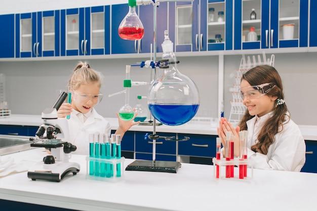 Zwei kleine kinder im laborkittel lernen chemie im schullabor. junge wissenschaftler in schutzbrillen machen experimente im labor oder im chemikalienschrank. zutaten für experimente untersuchen.