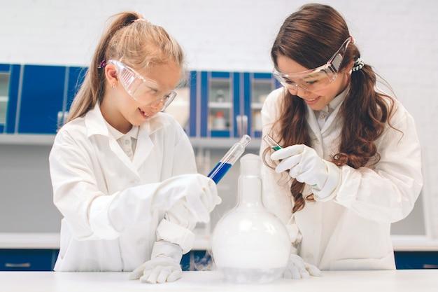 Zwei kleine kinder im laborkittel lernen chemie im schullabor. zutaten für experimente untersuchen. gefährliche experimente.