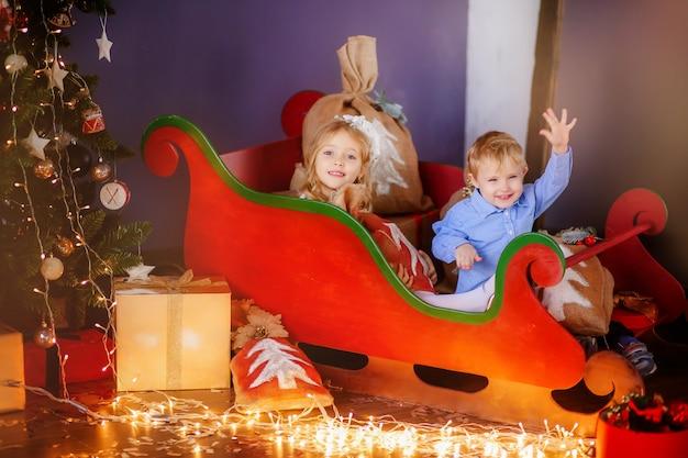 Zwei kleine kinder in der nähe mit einem weihnachtsbaum
