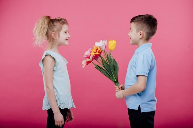 Zwei kleine kinder. kleiner junge streckt blumen zu einem kleinen mädchen im rosa kleid, lokalisiert auf blauer wand, profilansicht