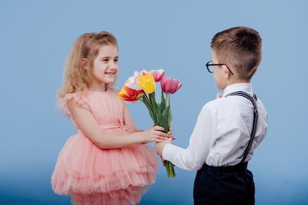 Zwei kleine kinder. kleiner junge streckt blumen zu einem kleinen mädchen im rosa kleid, lokalisiert auf blauer wand