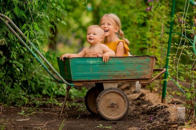Zwei kleine kinder mädchen und jungen auf dem land in einem garten schubkarre sitzen lächelnd