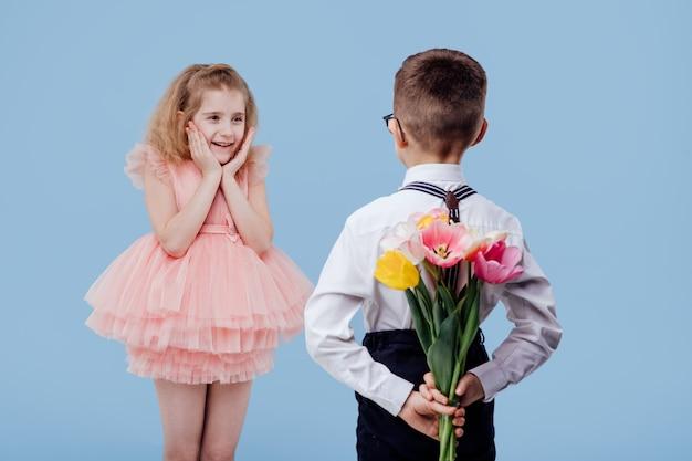 Zwei kleine kinderjunge mit blumen und überraschtem mädchen im rosa kleid, lokalisiert auf blauer wand