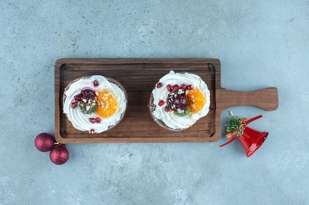 Zwei kleine kuchen auf einem holztablett auf marmor.