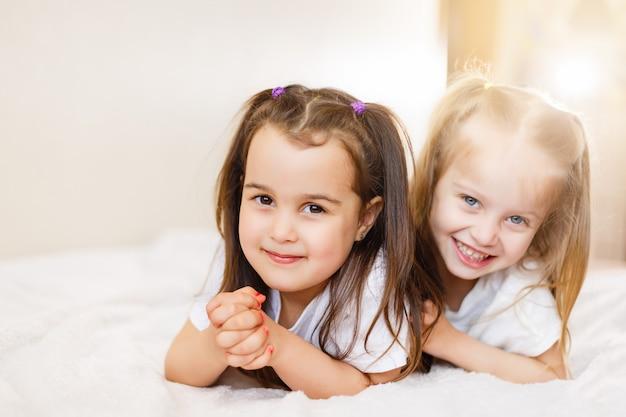 Zwei kleine lächelnde reizende schwestern im weißen bett, oberseite, ansicht