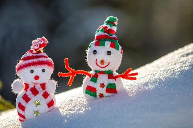 Zwei kleine lustige spielzeuge baby-schneemann in strickmützen und schals im tiefschnee im freien auf hellblauem und weißem kopierraumhintergrund. frohes neues jahr und frohe weihnachten grußkarte.