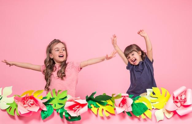 Zwei kleine mädchen auf sommer rosa wand