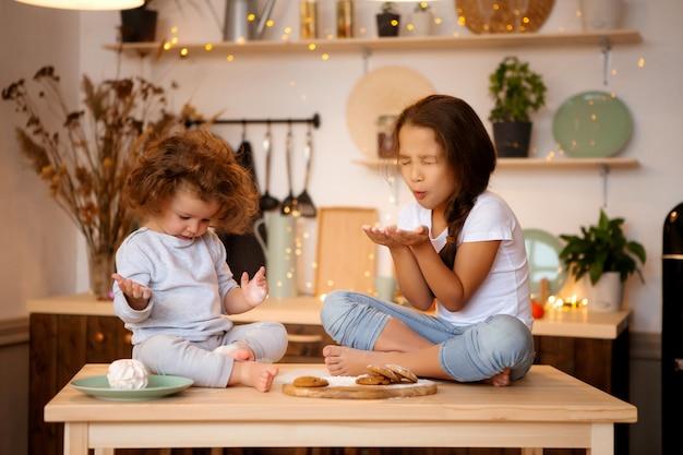 Zwei kleine mädchen bereiten weihnachtsplätzchen in der küche