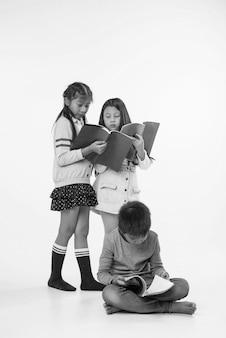 Zwei kleine mädchen, die an der rückseite des jungen stehen. sie lesen bücher, mit interessiertem gefühl, schwarzweiss-ton.