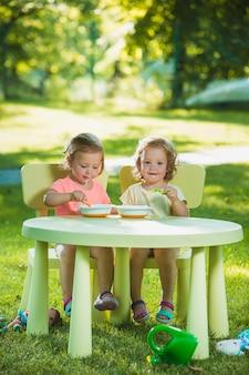 Zwei kleine mädchen, die an einem tisch sitzen und zusammen gegen grünen rasen essen