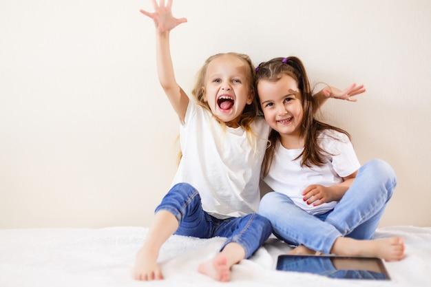 Zwei kleine mädchen, die eine notenauflagenfamilie, kinder, technologie und glückliche kleine mädchen des hauptkonzeptes verwenden