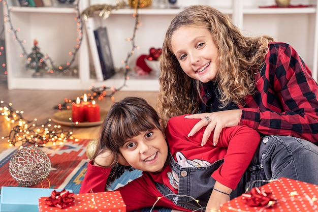 Zwei kleine mädchen, die glücklich mit dem weihnachtsgeschenk lächeln