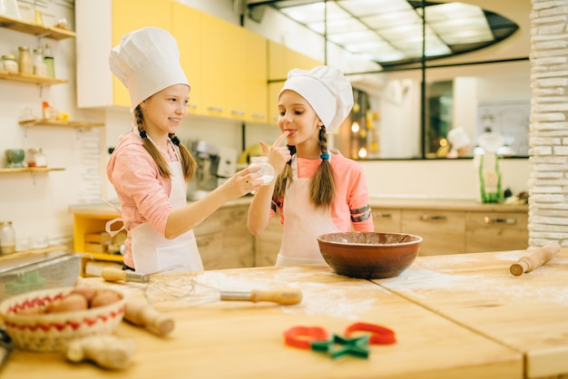 Zwei kleine mädchen, die in kappen kochen, schmecken süßes vanillepulver