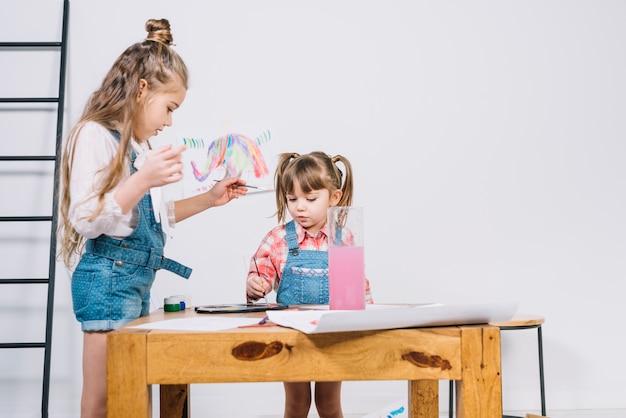 Zwei kleine mädchen, die mit aquarell auf papier malen