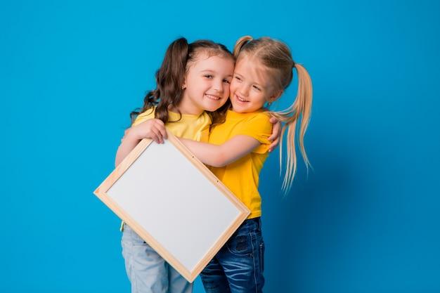 Zwei kleine mädchen, die mit einem leeren reißbrett auf einem blauen hintergrund lächeln