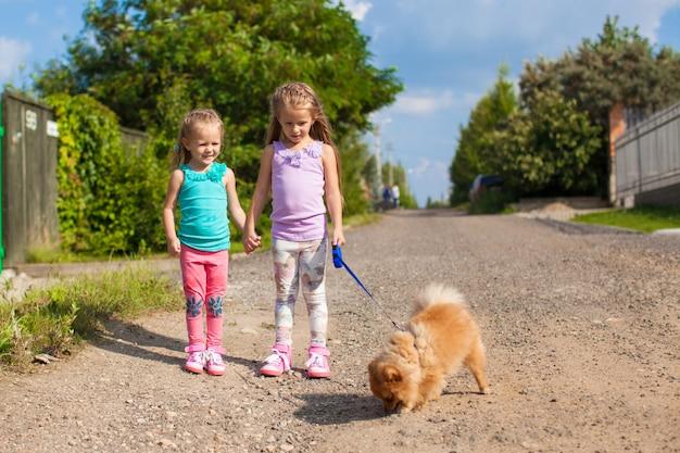 Zwei kleine mädchen, die mit kleinem hund auf einer leine im freien gehen