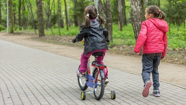 Zwei kleine mädchen fahren im frühjahr fahrrad im park
