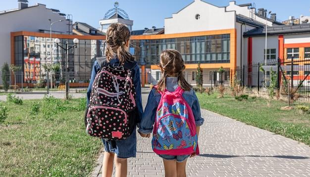 Zwei kleine mädchen gehen zur schule, halten sich an den händen, rückansicht.
