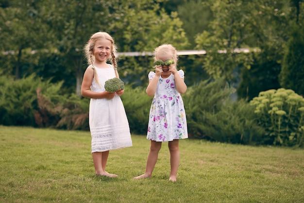 Zwei kleine mädchen in sarafans und zöpfen in einem grünen garten halten brokkoli in ihren händen. sie schließen die augen und lachen. gesundes lebensmittelkonzept, grünes vegetarisches essen.