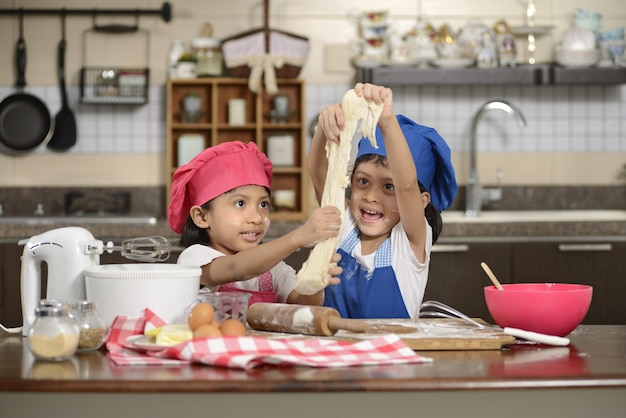 Zwei kleine mädchen machen pizza