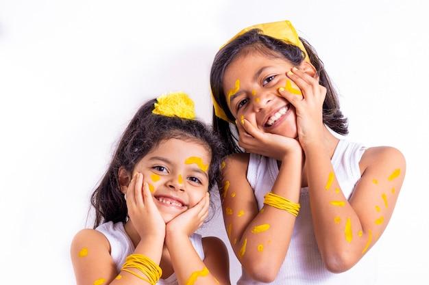 Zwei kleine mädchen, mit ihrem gesicht gemalt, um den gelben tag zu feiern