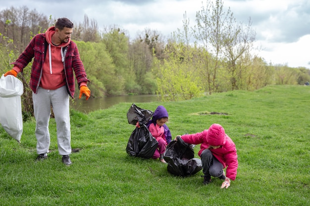 Zwei kleine mädchen mit ihrem papa, mit müllsäcken auf einem ausflug in die natur, reinigen die umwelt.