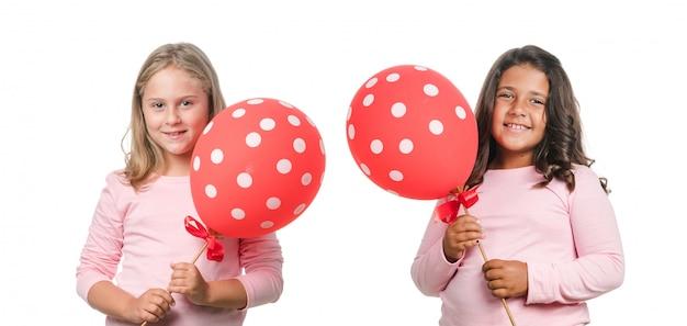 Zwei kleine mädchen mit rotem ballon