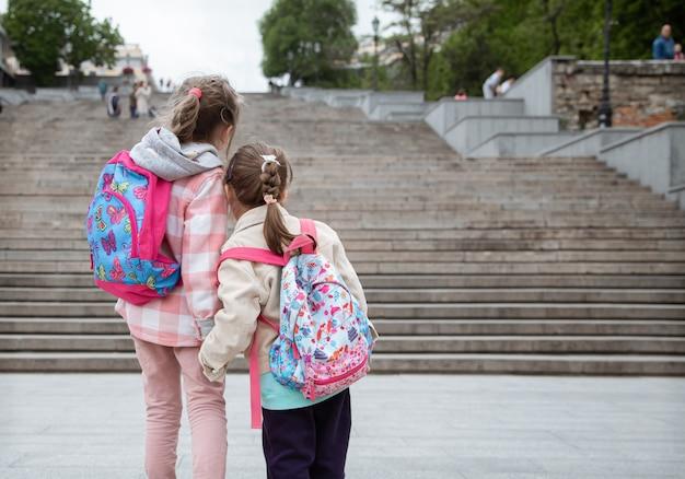 Zwei kleine mädchen mit rucksäcken auf dem rücken gehen hand in hand zur schule. kindheitsfreundschaft