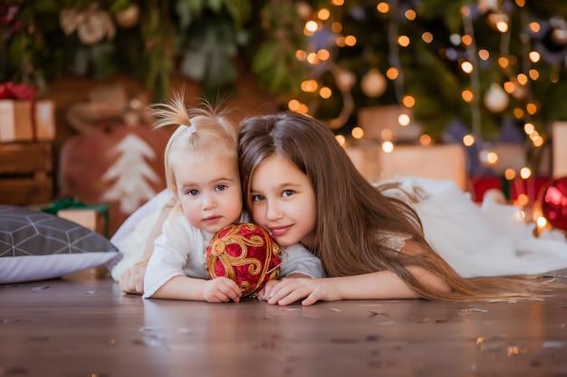 Zwei kleine mädchen neben dem weihnachtsbaum