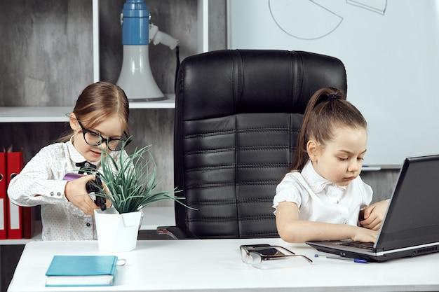 Zwei kleine mädchen posieren als büroangestellte, die an einem laptop arbeiten und blumen gießen