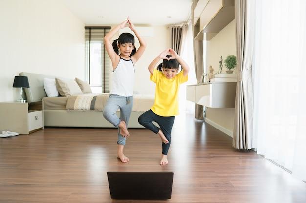 Zwei kleine mädchen praktizieren yoga, stretching, fitness per video auf dem notebook.