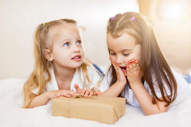 Zwei kleine mädchen schwestern geben geschenke kinder mädchen open present gift box