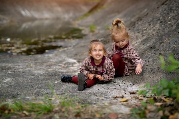Zwei kleine mädchen sitzen auf felsen in einer felsigen gegend
