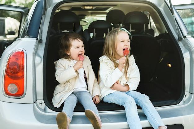 Zwei kleine mädchen sitzen im kofferraum eines autos und essen lutscher