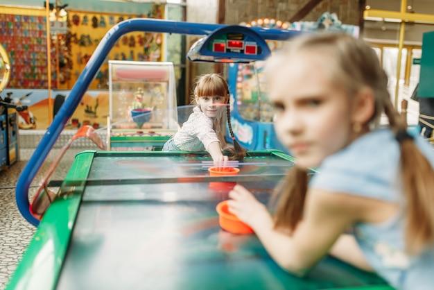 Zwei kleine mädchen spielen airhockey im spielzentrum