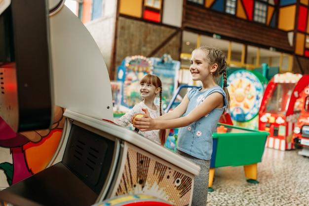 Zwei kleine mädchen spielen auf videospielmaschine