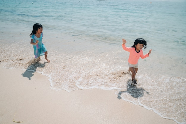 Zwei kleine mädchen spielen verfolgungsjagd im strand