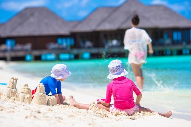 Zwei kleine mädchen und glückliche mutter, die mit strandspielwaren auf sommerferien spielen