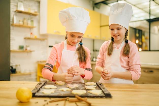 Zwei kleine mädchenköche bereiten sich darauf vor, kekse in den ofen zu schicken