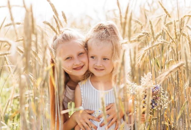 Zwei kleine mädchenschwestern umarmen und sammeln blumen im sommer